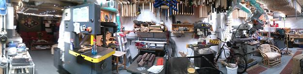 "This is the north wall of the shop. Pictured from left is the entrance and interior of the office, the 19"" Powermatic band saw, the shaft machine and the cabinet saw, the mill drill, a J-head Mitek milling machine, and finally the Smithy lathe that I have been using for the last 18 or so years. Notice the green piping that is used for dust collection."